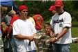Two men posing with the catch and a young boy