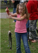 Young girl holding her fish on a line